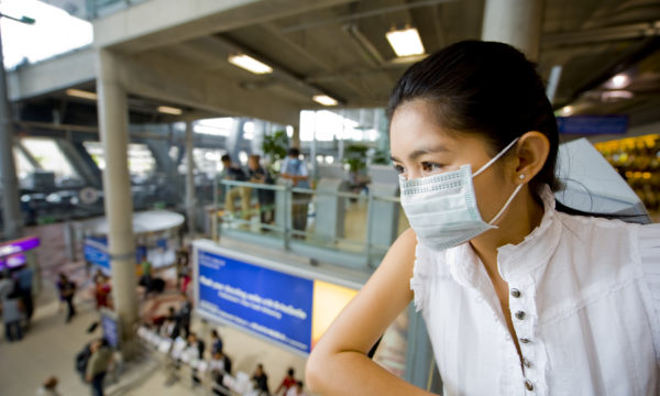 woman at airport wearing face mask